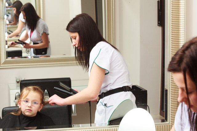 Hairdresser straightening hair little girl child in hairdressing beauty salon