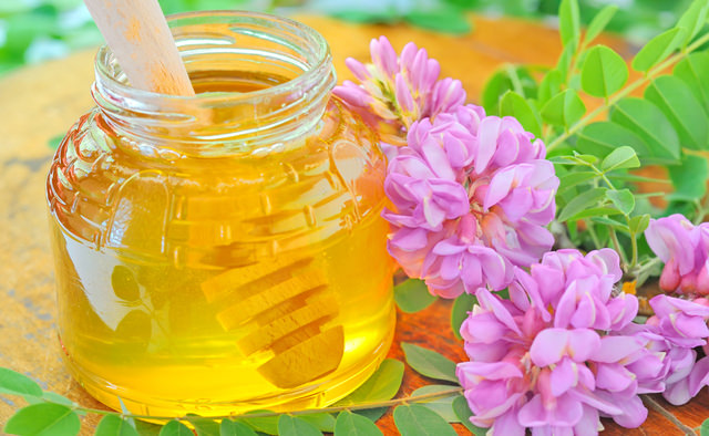 glass jar full of honey and stick with acacia pink and white flo