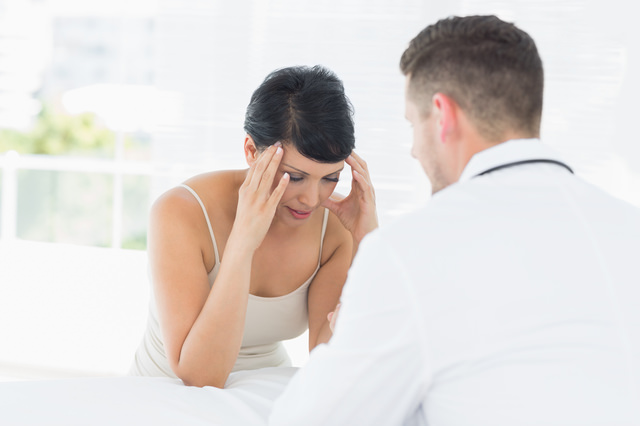 Stressed woman visiting male doctor in clinic