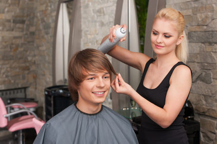 blond female hairstylist using hair spray.