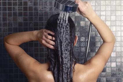 Attraktive Frau wscht ihre Haare in der Dusche