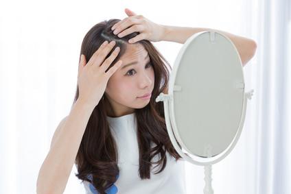 髪の分け目を変える女性