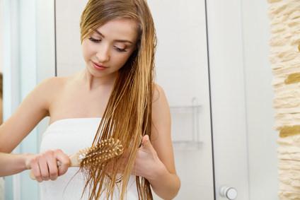 Hair. Beautiful Blond Brushing Her Wet Hair. Hair Care.