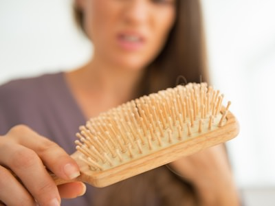 Closeup on stressed young woman looking on hair comb
