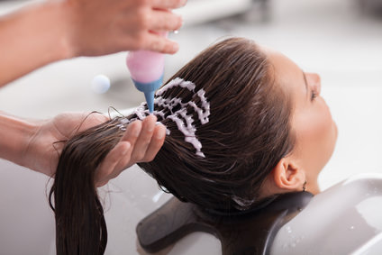 Attractive young girl is getting a hairwash in salon