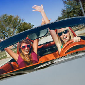 Young women enjoying life in a convertable sports car.